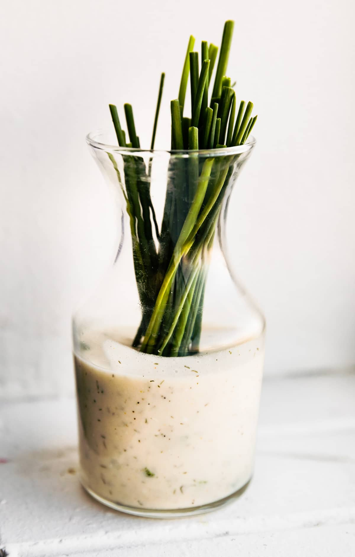 scallions standing in tall pitcher of spicy vegan ranch dressing
