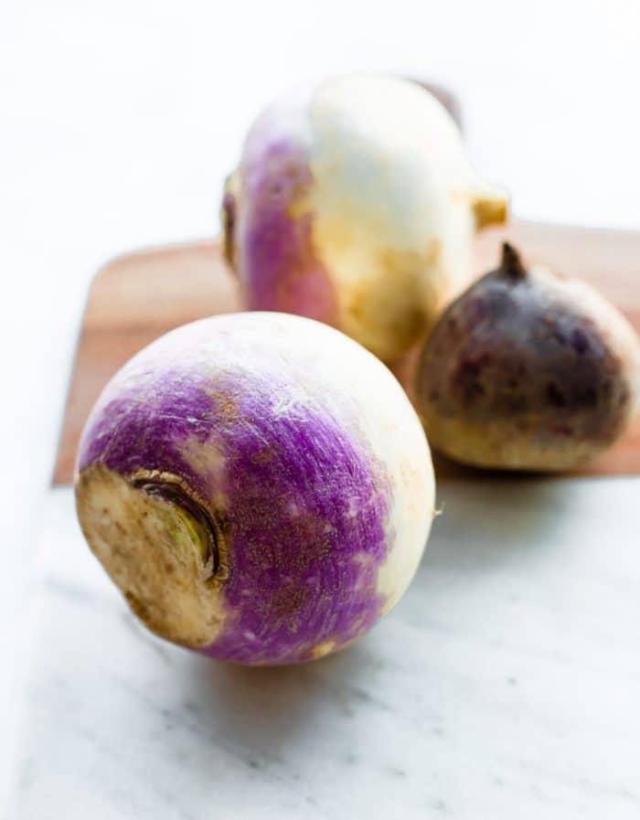 whole raw turnips on a cutting board