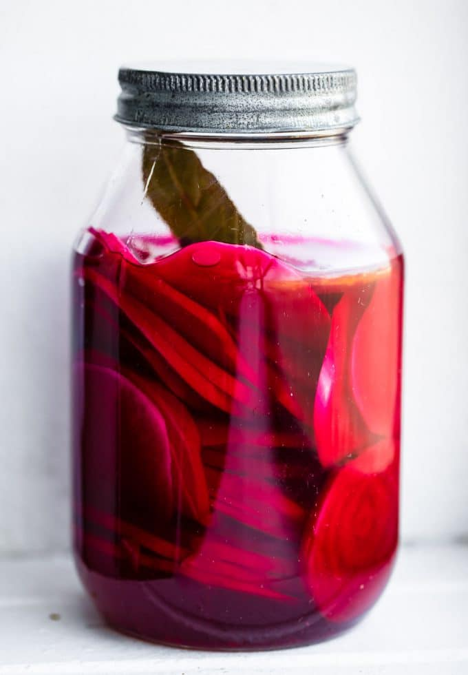 turnip pickles and bay leaf in a glass canning jar