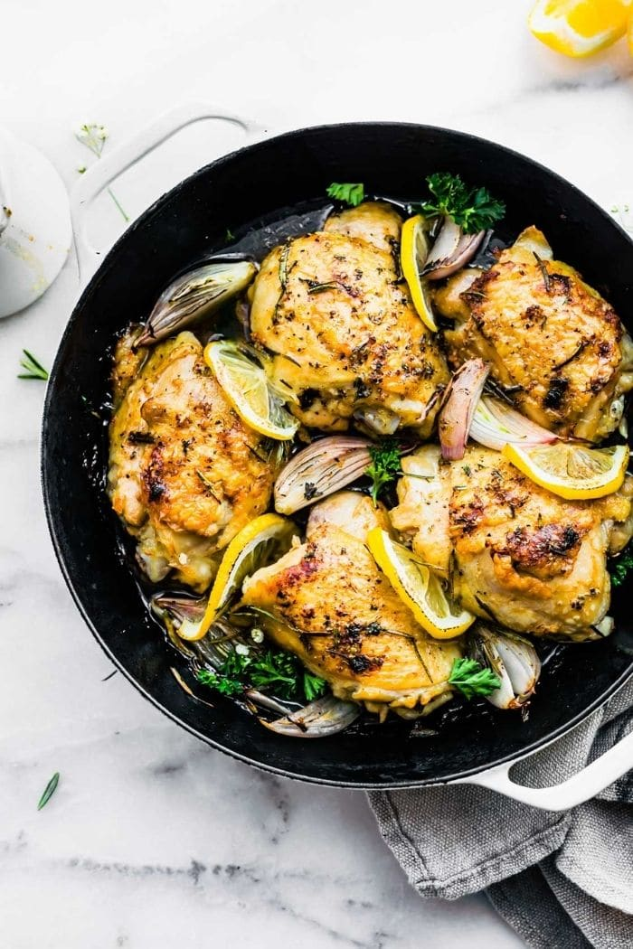 bone-in chicken thighs with crispy skin in skillet with lemon slices and onions