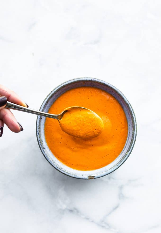 overhead: spoonful of roasted red pepper sauce over bowl of sauce
