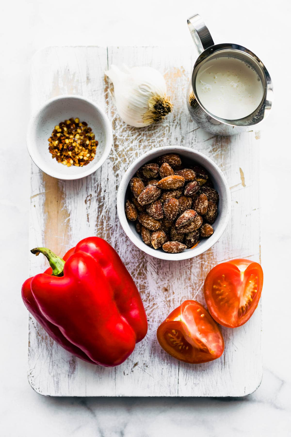ingredients to make roasted red pepper sauce on white wooden cutting board