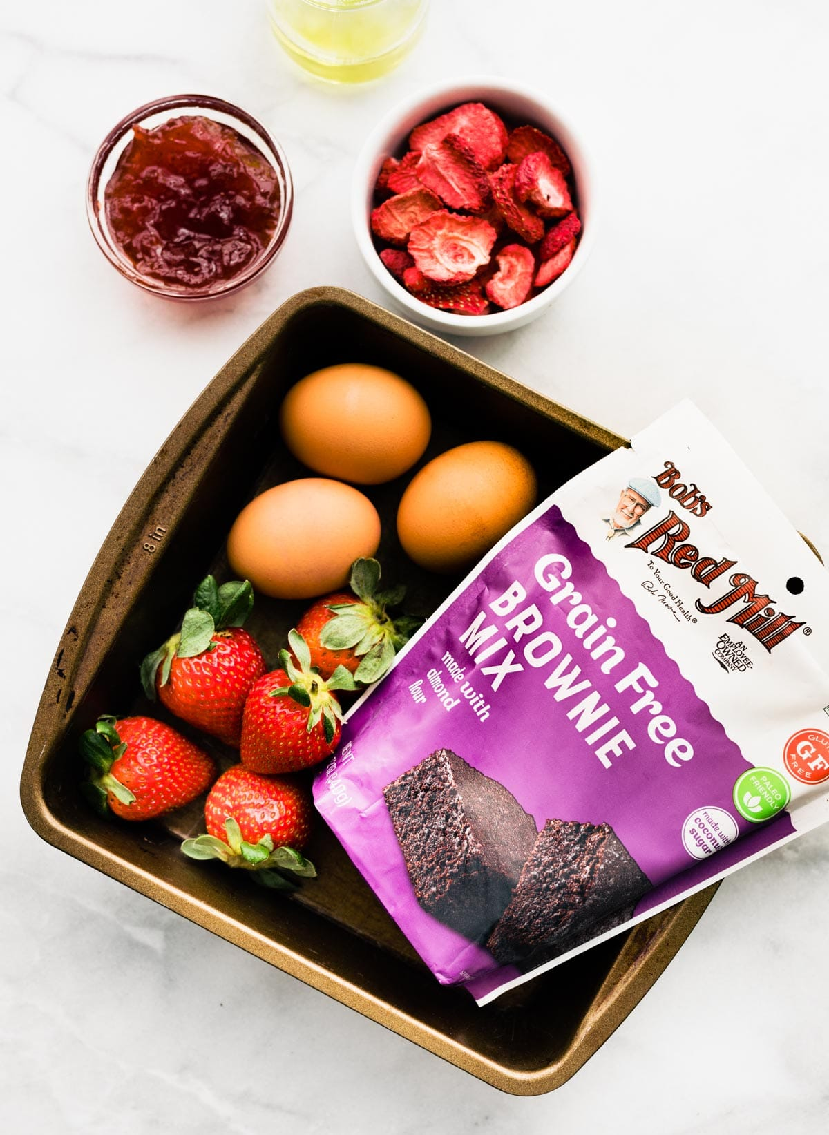 overhead photo: eggs, strawberries and package of grain free brownie mix in square baking pan