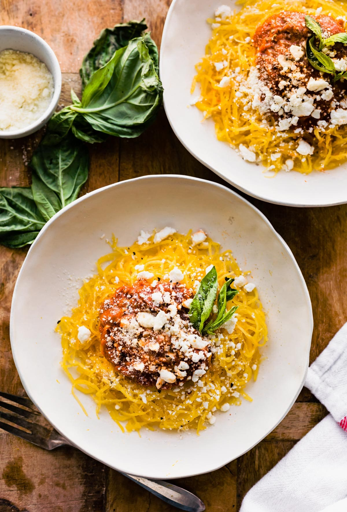 overhead: 2 plates of spaghetti squash pasta topped with tomato sauce alternative