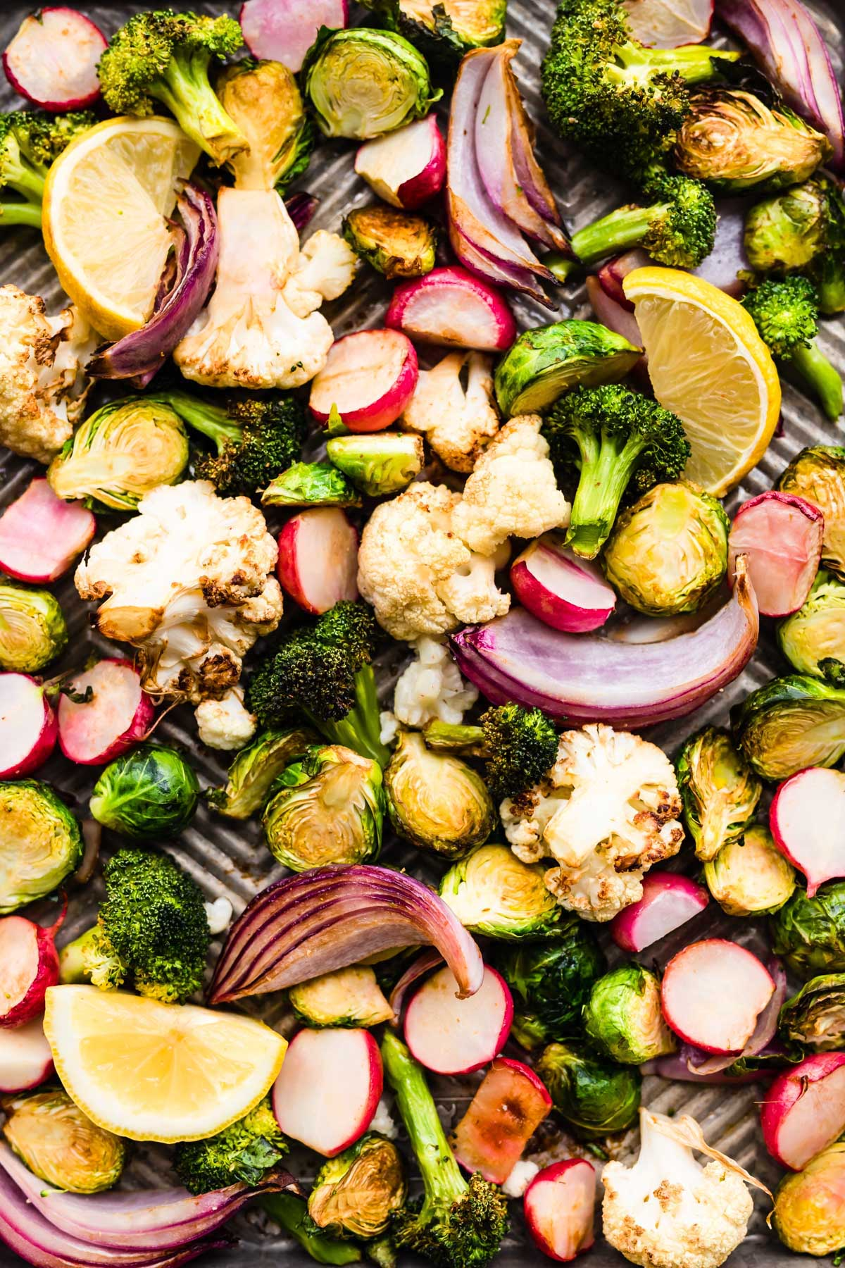 close up image of air fryer veggies (broccoli, cauliflower, radishes, Brussels sprouts and red onion