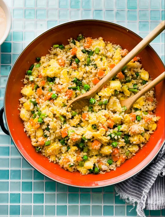 overhead image: two serving spoons in skillet of homemade healthy fried rice