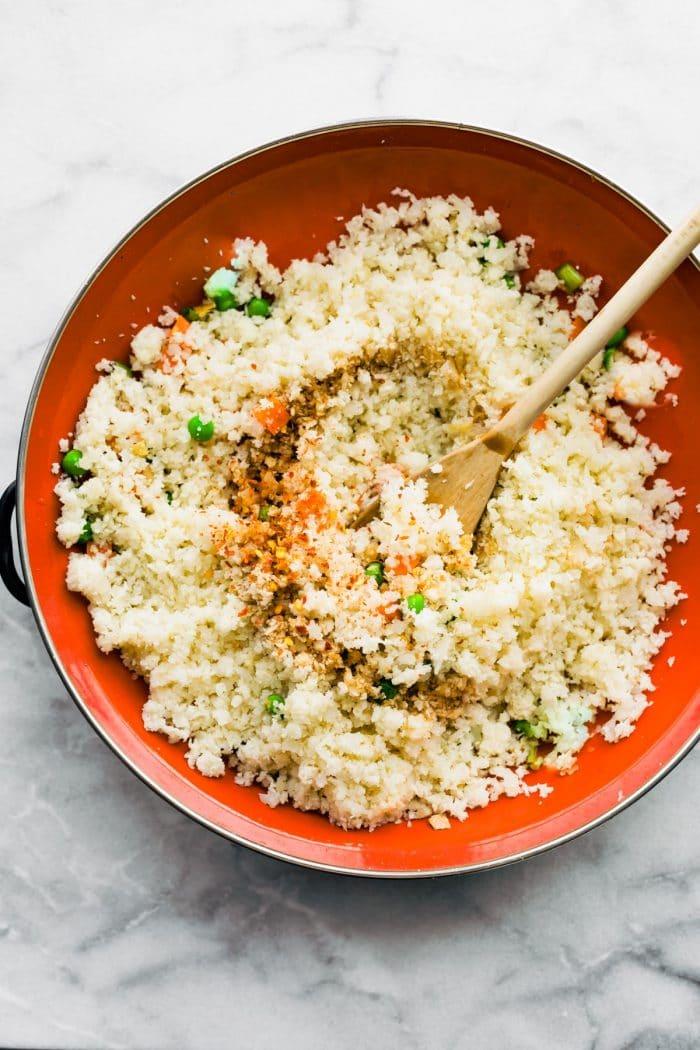 stir frying cauliflower rice in skillet