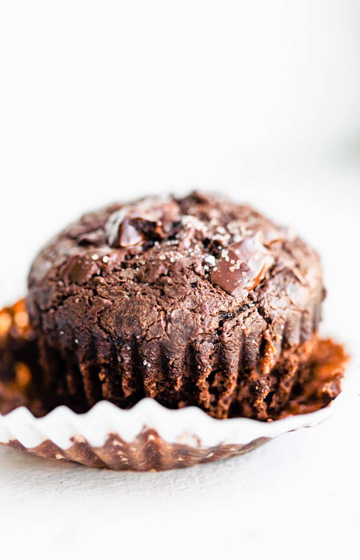 one fluffy gluten free chocolate muffin topped with sea salt on white paper cupcake liner