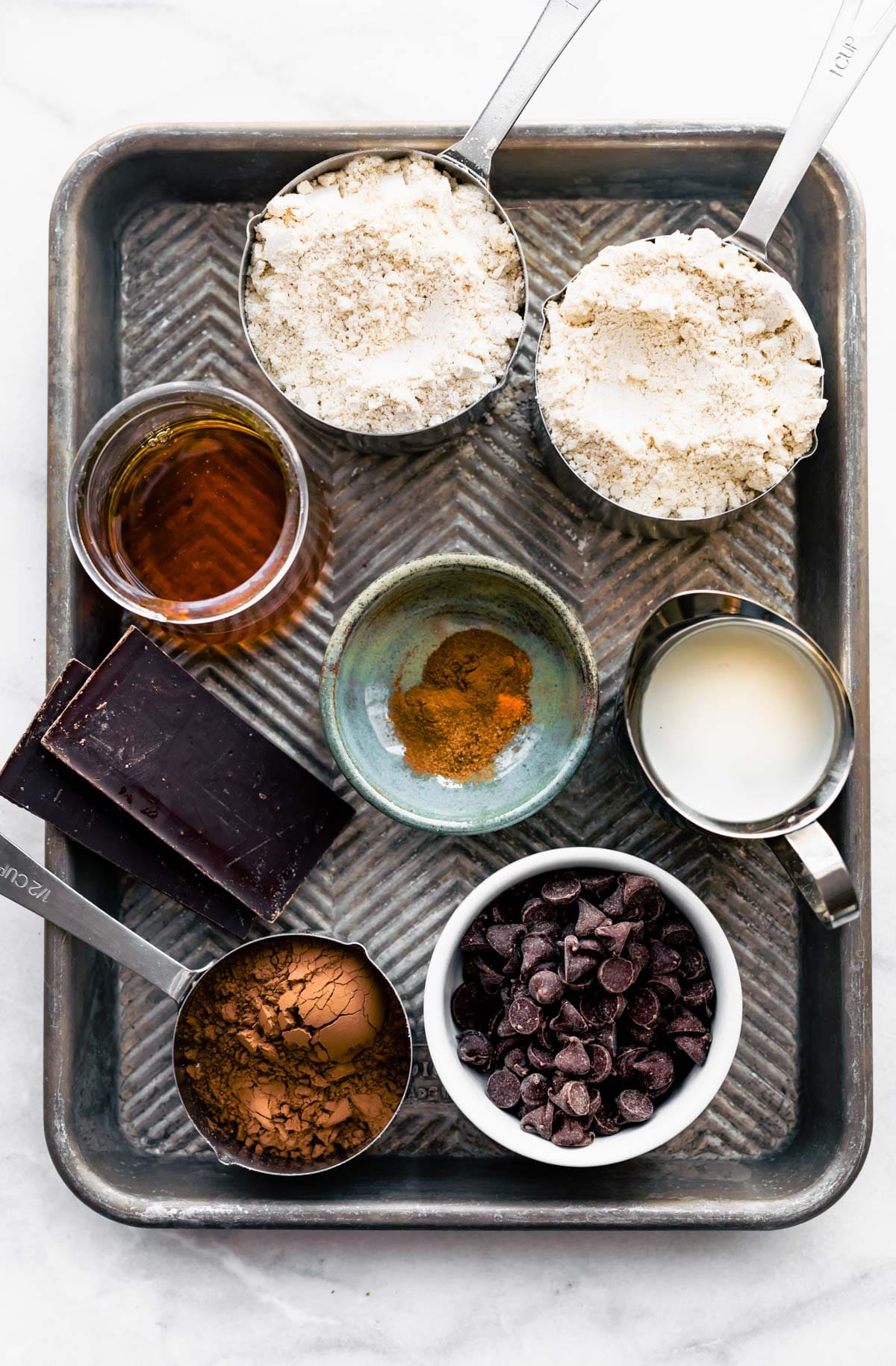 measuring cups and prep bowls filled with ingredients for a dark chocolate vegan muffin recipe
