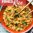 titled image (and shown in bowl with wooden spoons): pineapple cauliflower fried rice