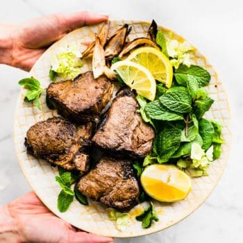 a hand holding a plate with lamb chops, fresh mint, and sliced lemon