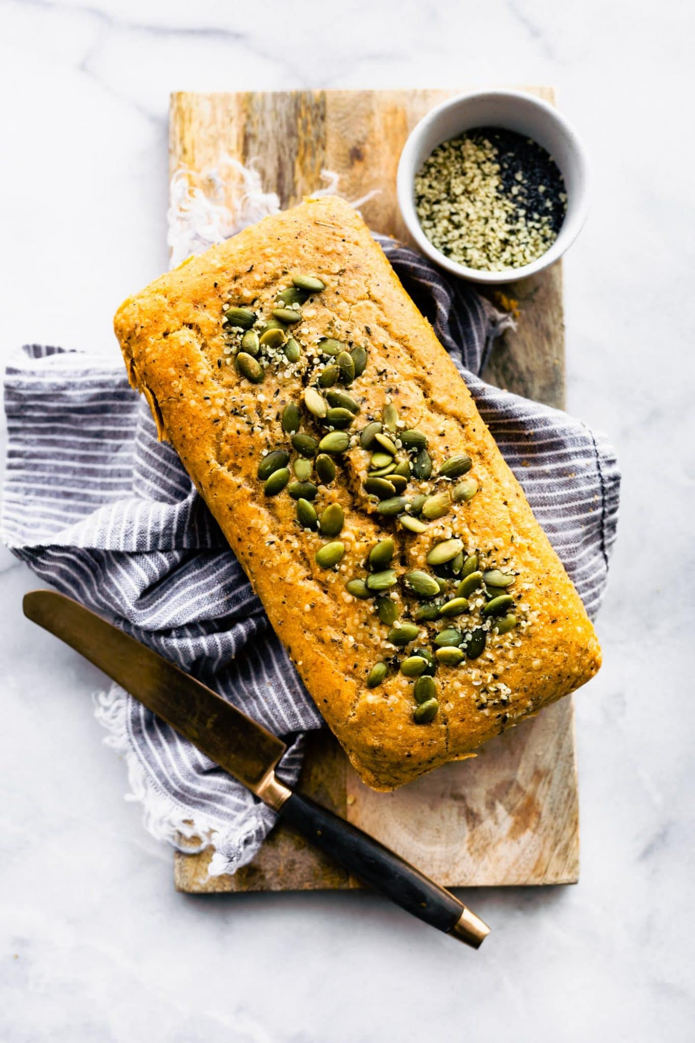 A loaf of nutty paleo bread with seeds on top on a blue napkin on a wooden cutting board with a black knife