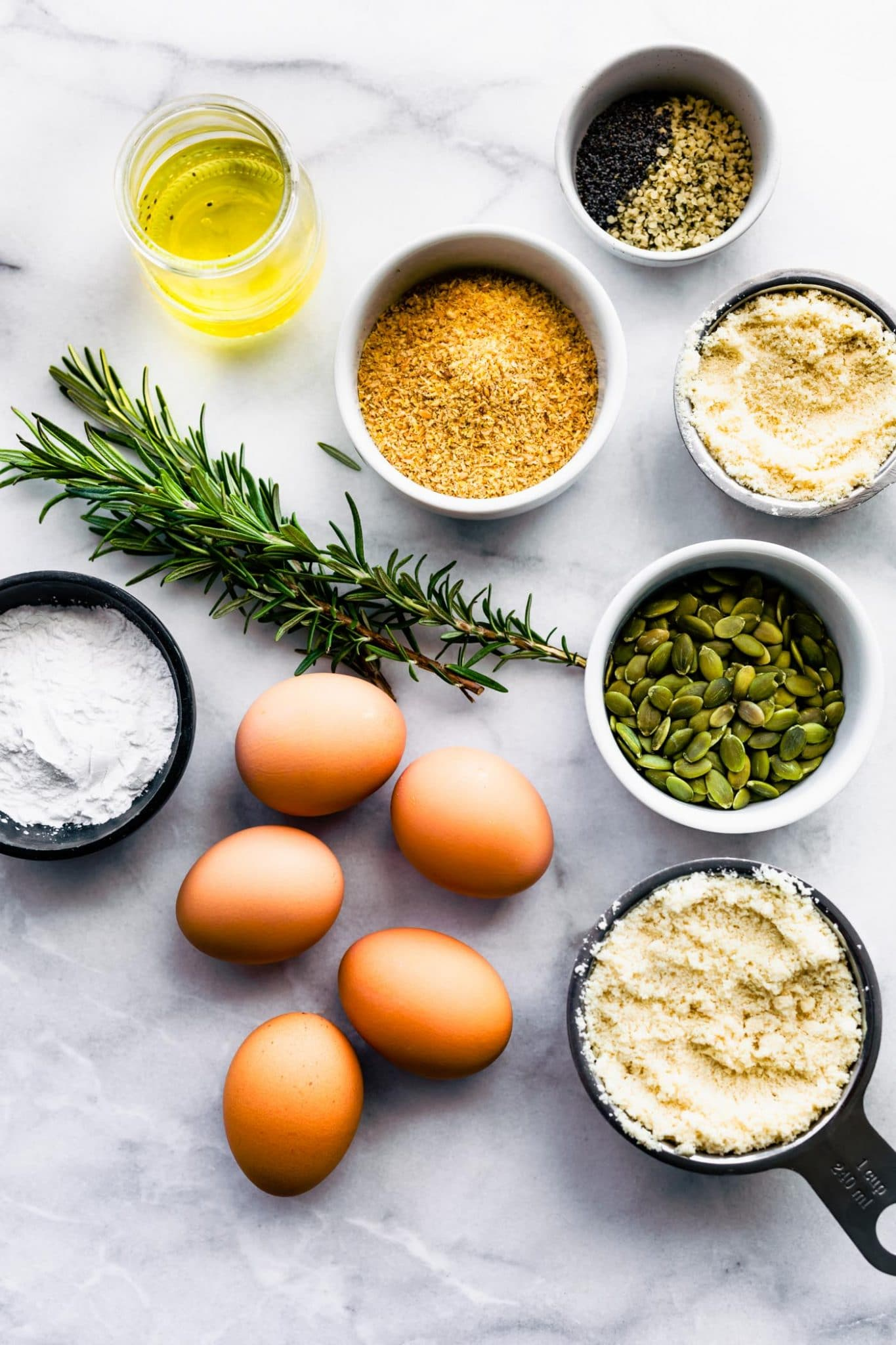 small ramekins of almond flour, tapioca starch, baking soda, flaxseed meal, eggs, pumpkin seeds, and rosemary on a white marble countertop
