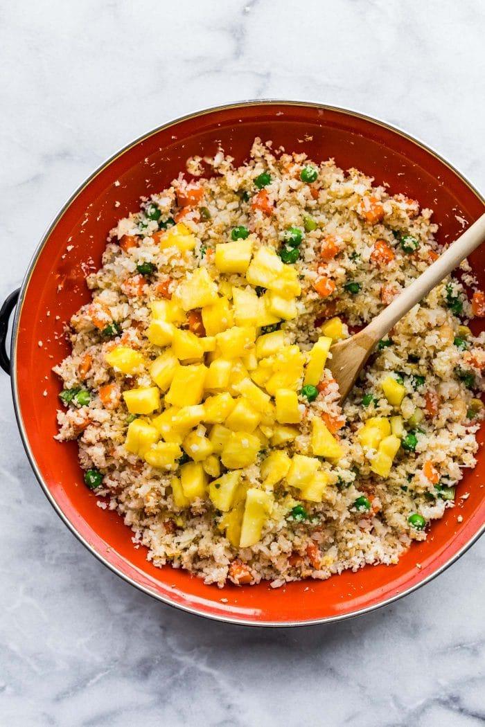 stirring pineapple into skillet of cauliflower fried rice