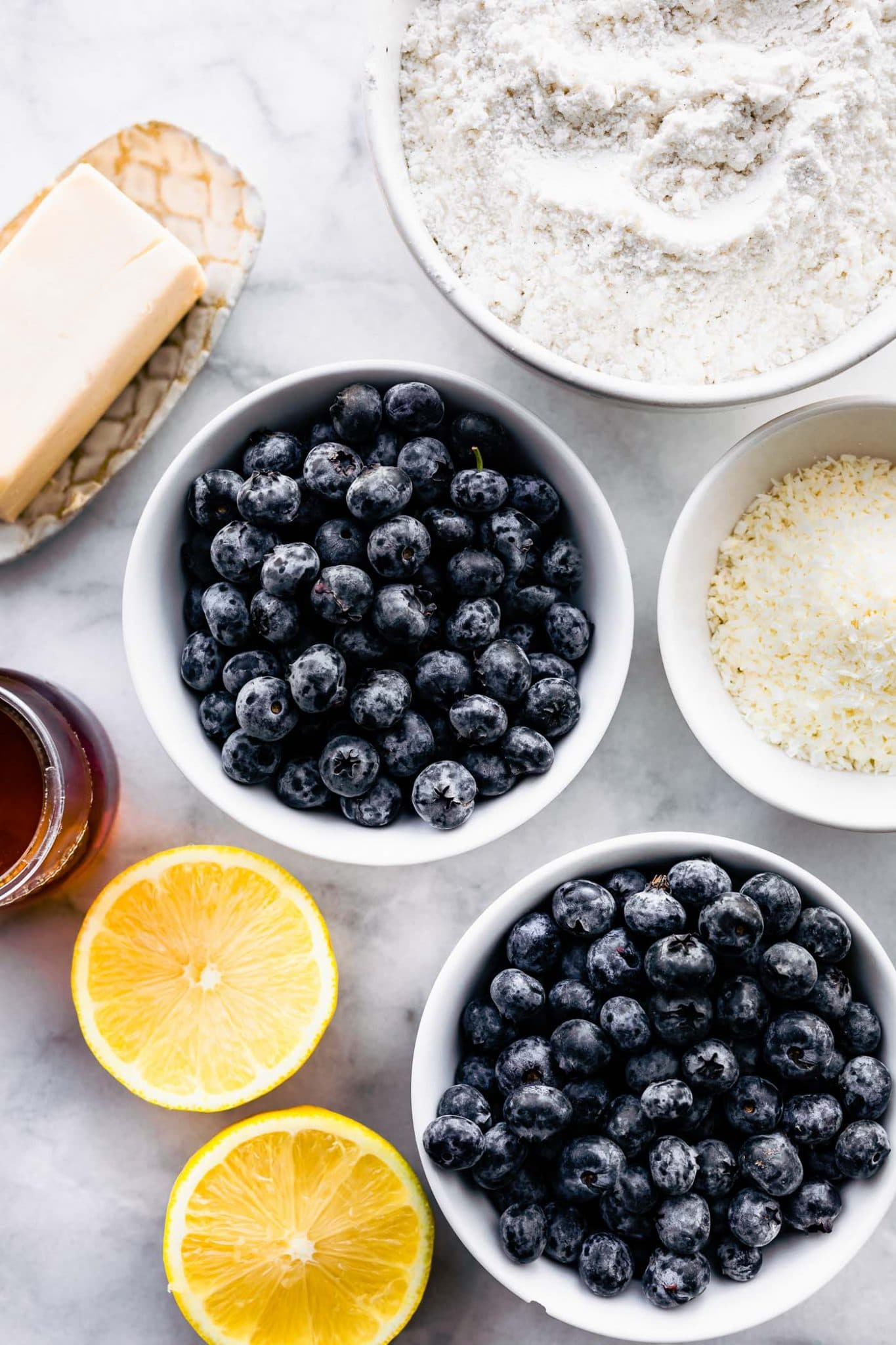 overhead photo: blueberries in a bowl, sliced in half lemon, coconut flakes in a bowl, stick of butter on a plate, bowl of gluten free flour