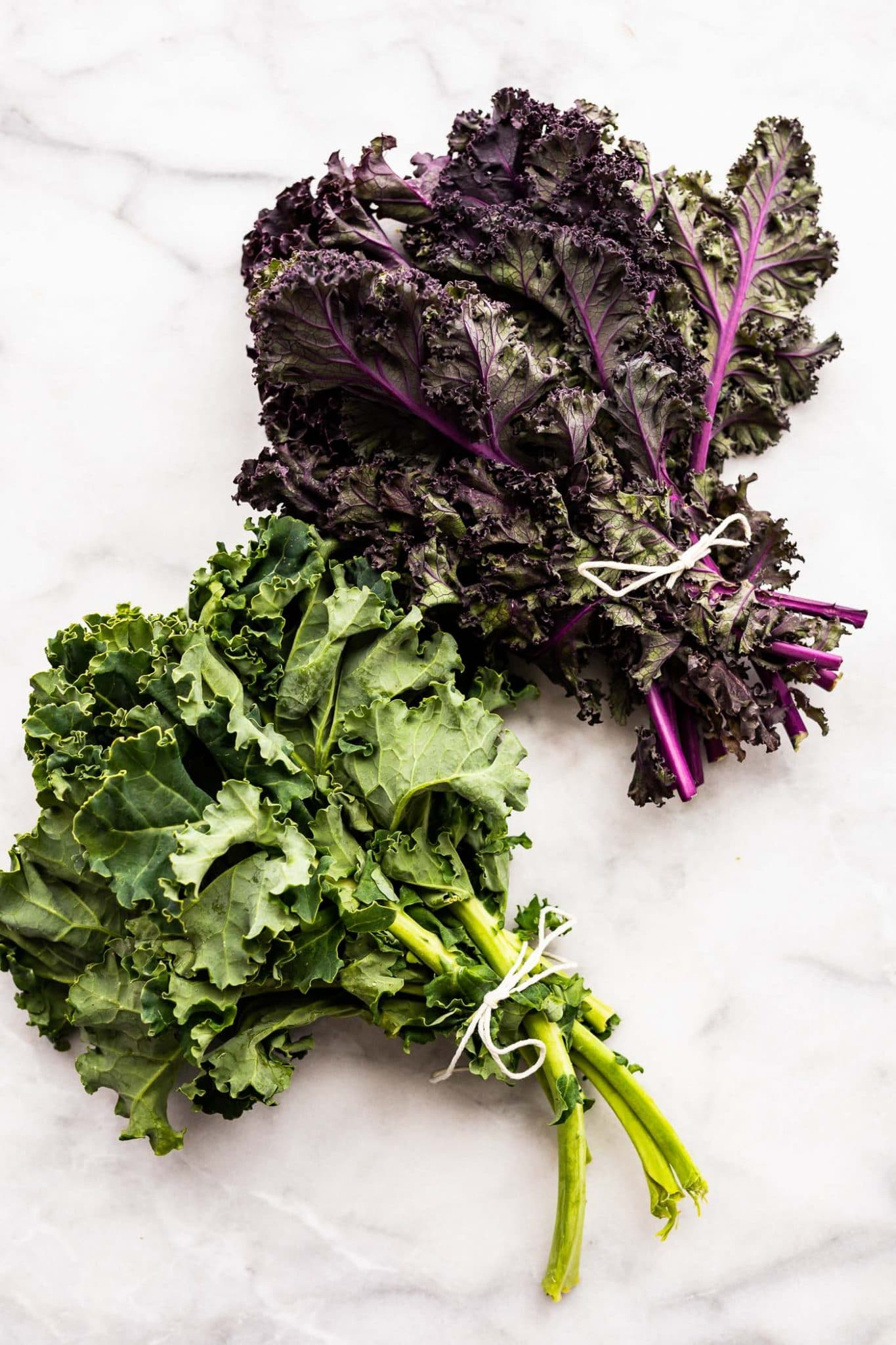 overhead photo of 2 bunches of kale; purple and green