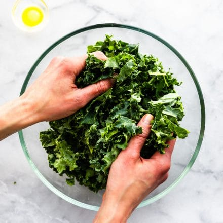 overhead photo of womans' hands massaging kale in glass bowl