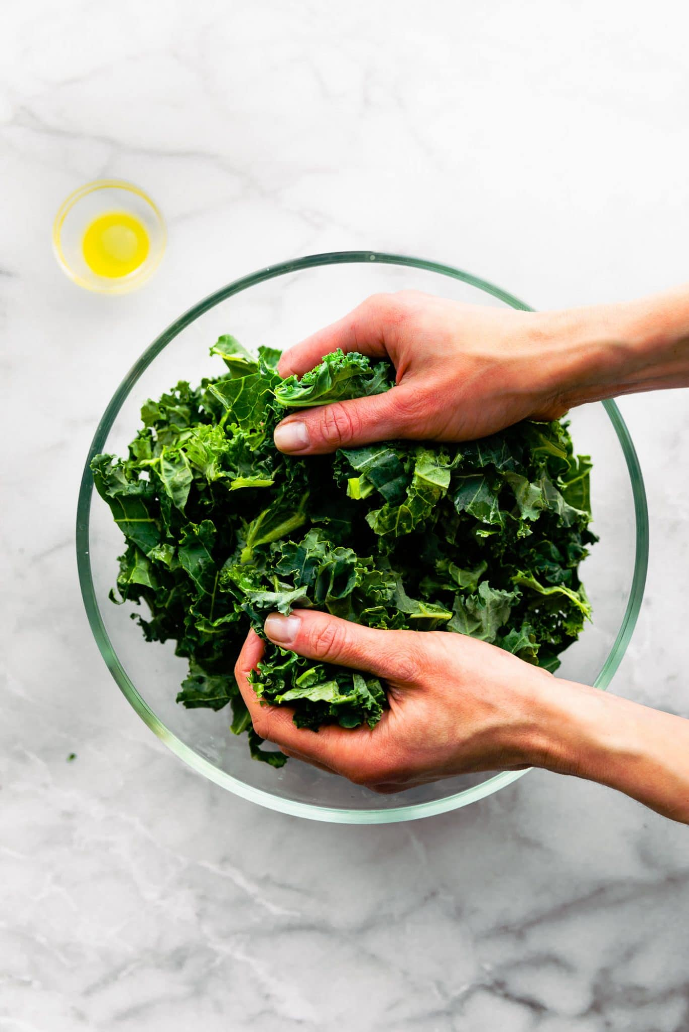 overhead photo of womans' hands softening kale by massaging kale in glass bowl