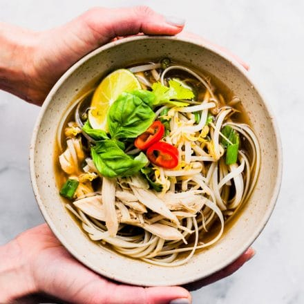 woman's hands holding bowl of gluten free pho ga with rice noodles
