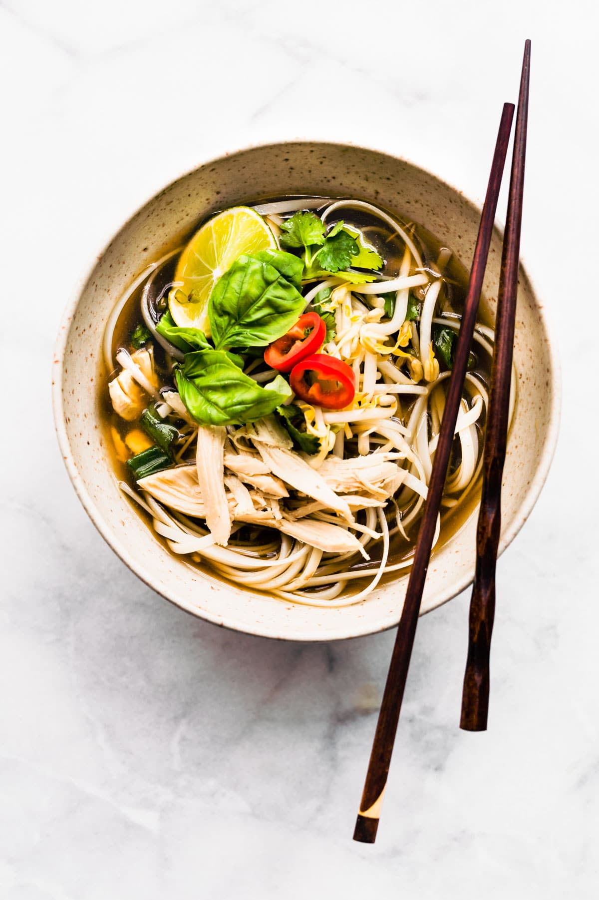 chopsticks on bowl of chicken pho ga with rice noodles