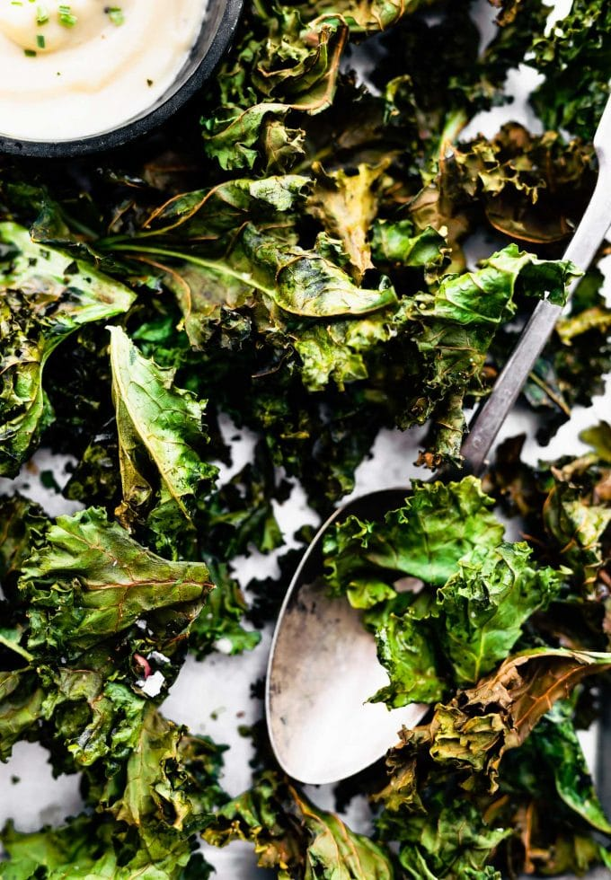 Detail shot of seasoned, crispy kale chips on a sheet pan