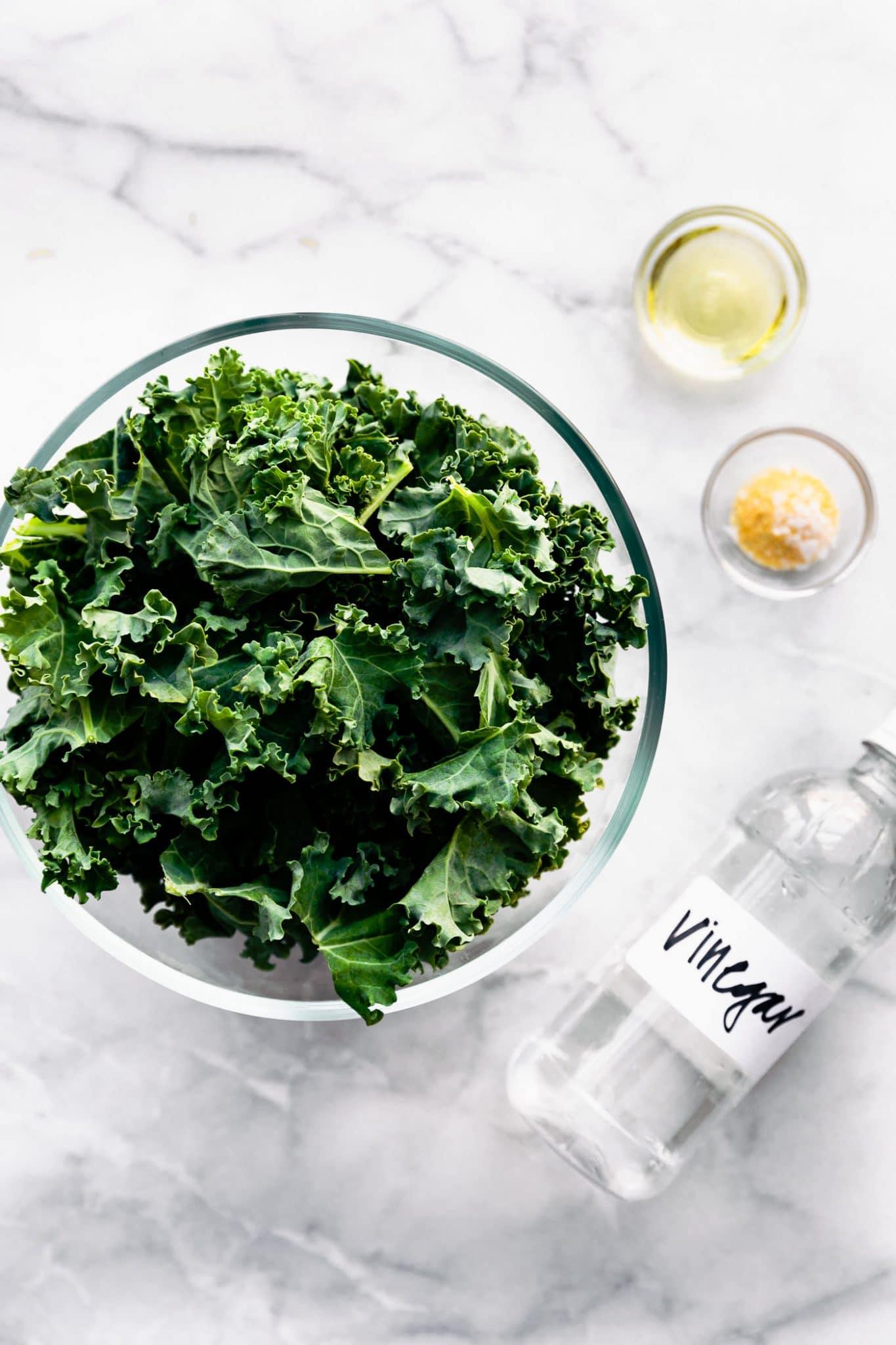 Air fryer kale chips in a bowl alongside seasonings: Garlic powder, vinegar, and sea salt