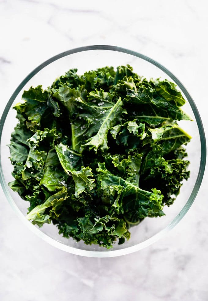 Crispy kale chips inside a large bowl before seasoning