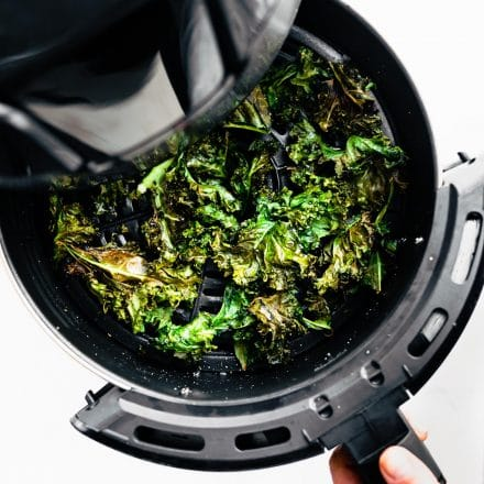 Baked salt and vinegar kale chips being pulled out of the air fryer