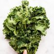 overhead photo of womans' hands massaging kale in glass bowl and title post in black writing - benefits of kale and how to massage it