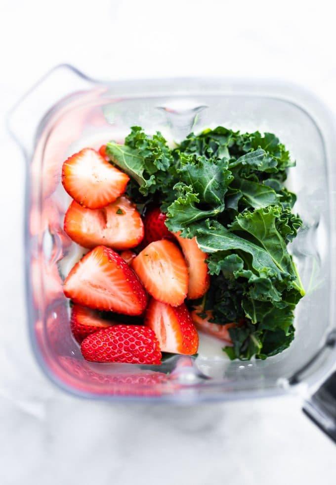 Fresh sliced strawberries and softened kale inside a blender