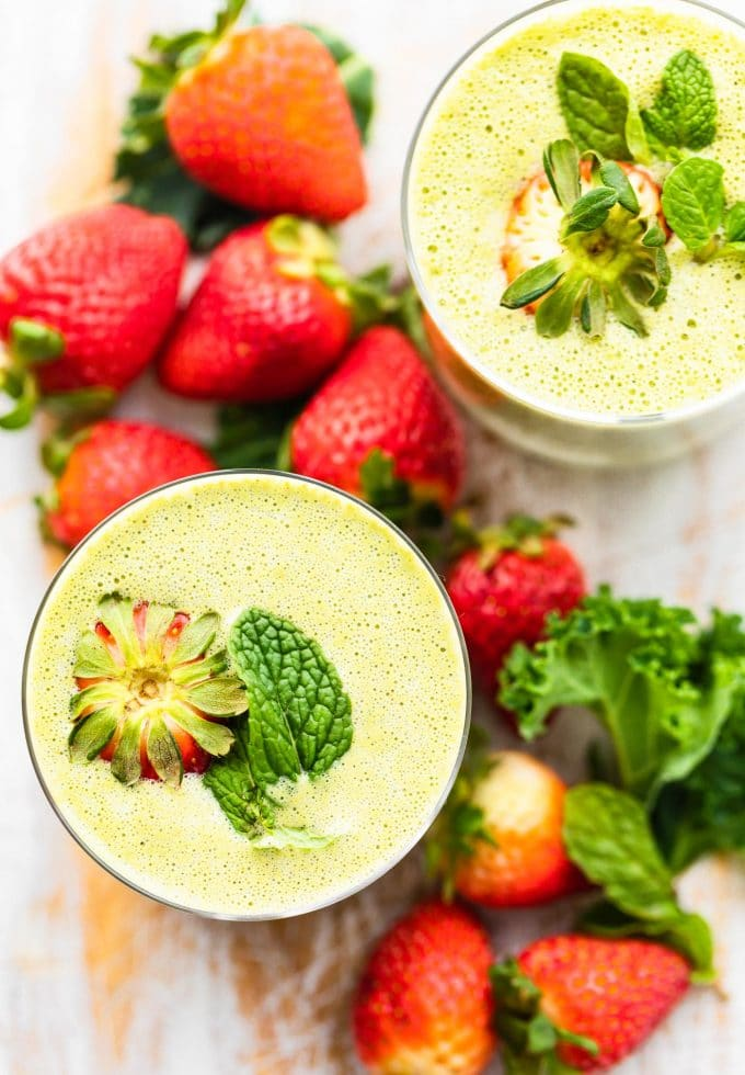 overhead shot of kale smoothie with strawberries in the background. Mint and strawberries on top of each glass of smoothie