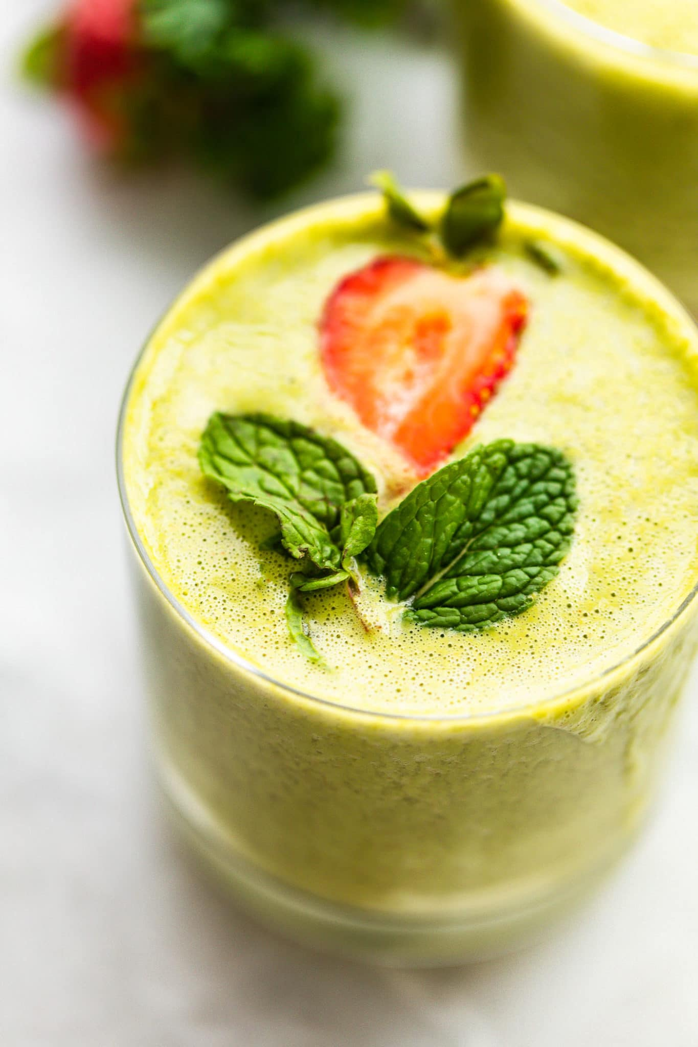 Image of a glass filled with blended super fruit kale smoothie, topped with fresh mint and strawberry