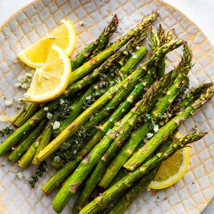 Overhead image of air fryer roasted asparagus on a plate with thin wedges of lemon.