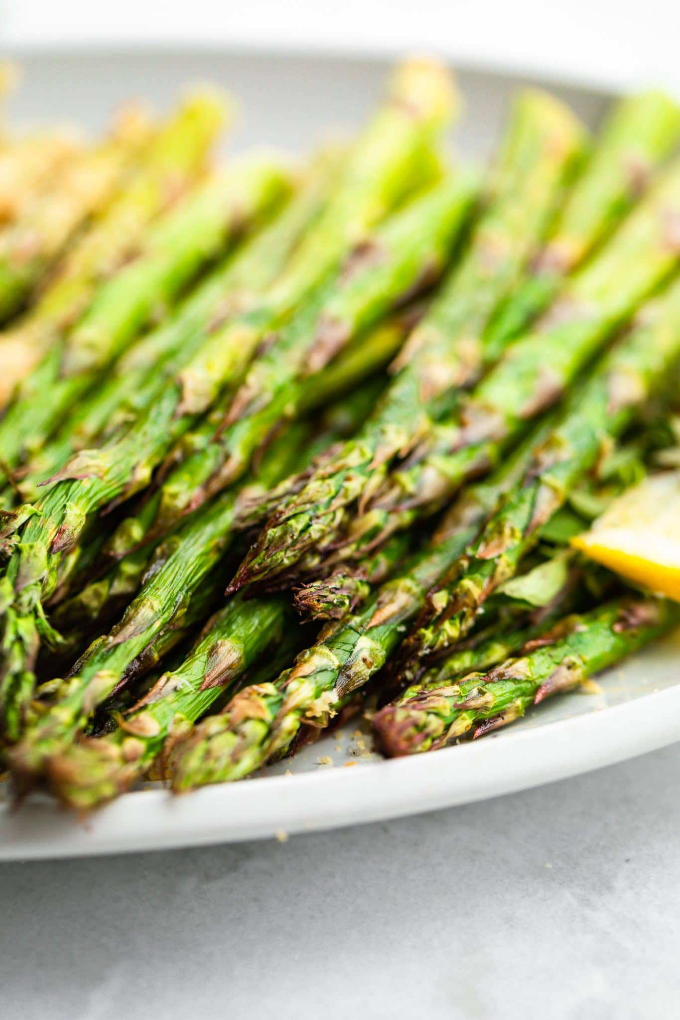 Side close up image of asparagus spears on a dish.