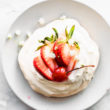 An overhead image of a pavlova on a white plate, topped with fresh strawberries and a cherry.