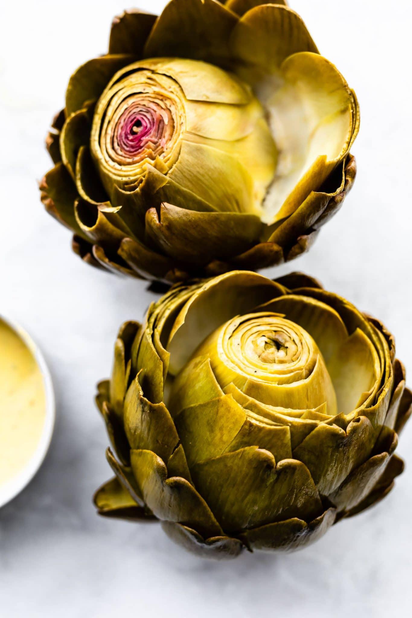 A close up image of prepared fresh artichokes with a side dish of garlic aioli.