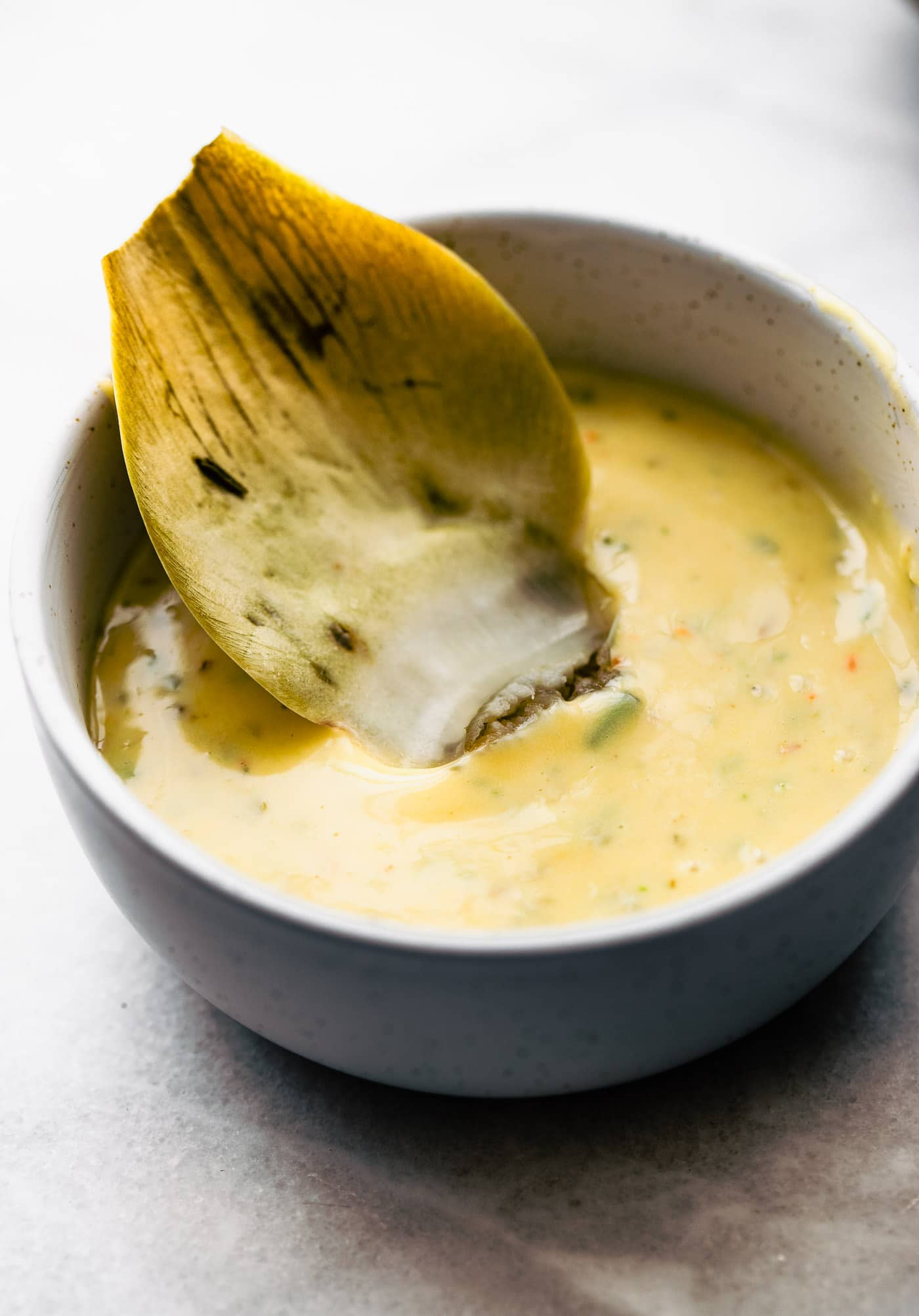 A close up image of a small bowl with garlic and herb aioli as a condiment for dipping artichokes and other vegetables.