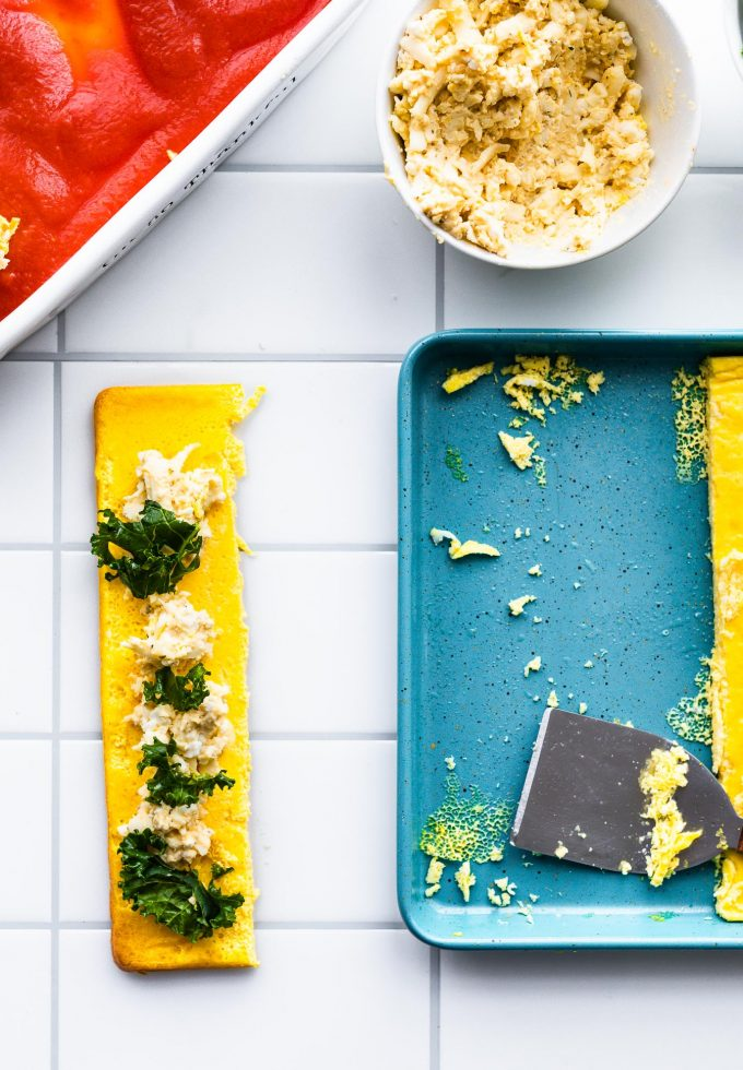 Sliced egg noodles are spread with hummus/cheese mixture and spinach before rolling