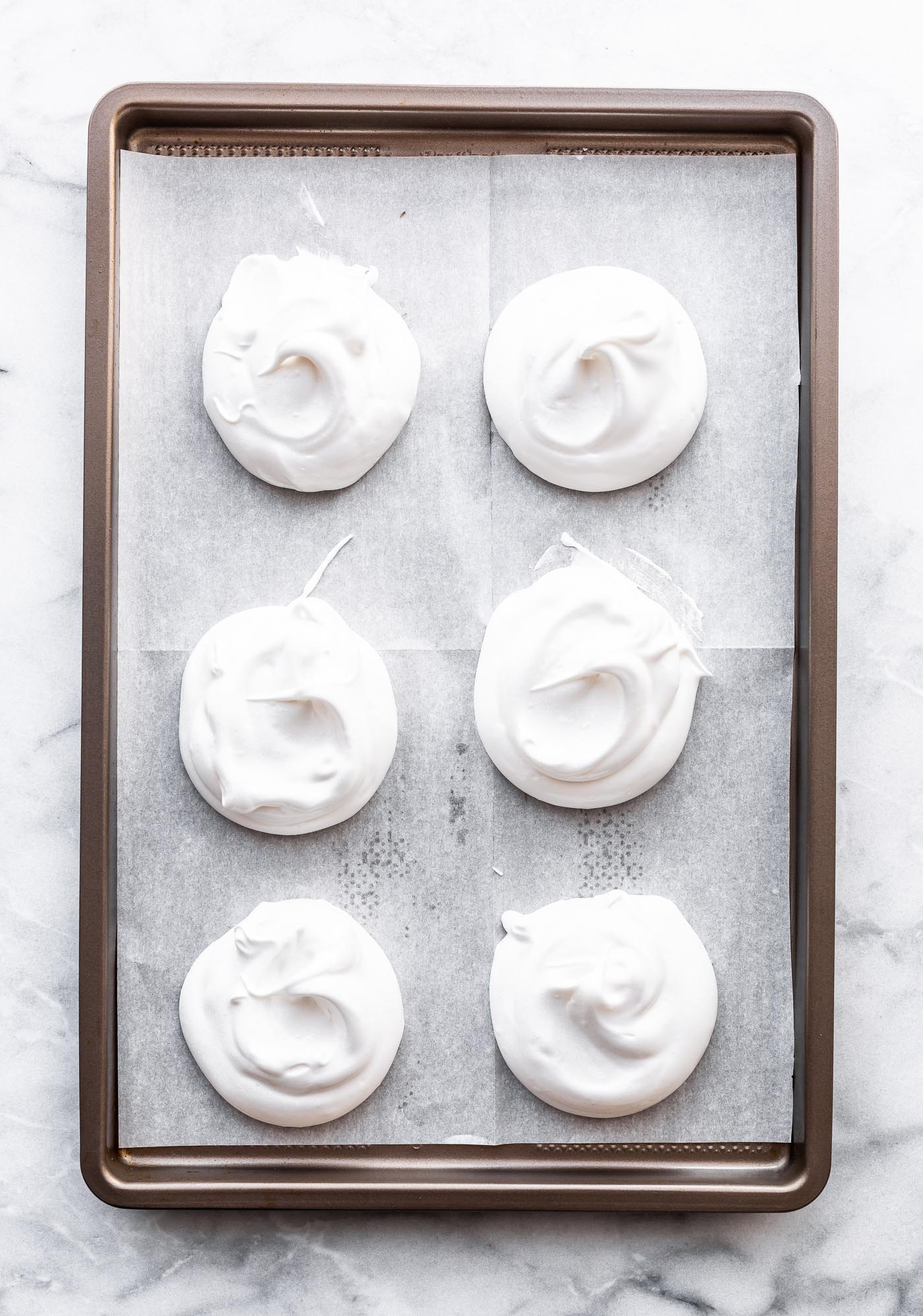 Overhead image of pavlovas pre-baked on a parchment lined sheet pan.