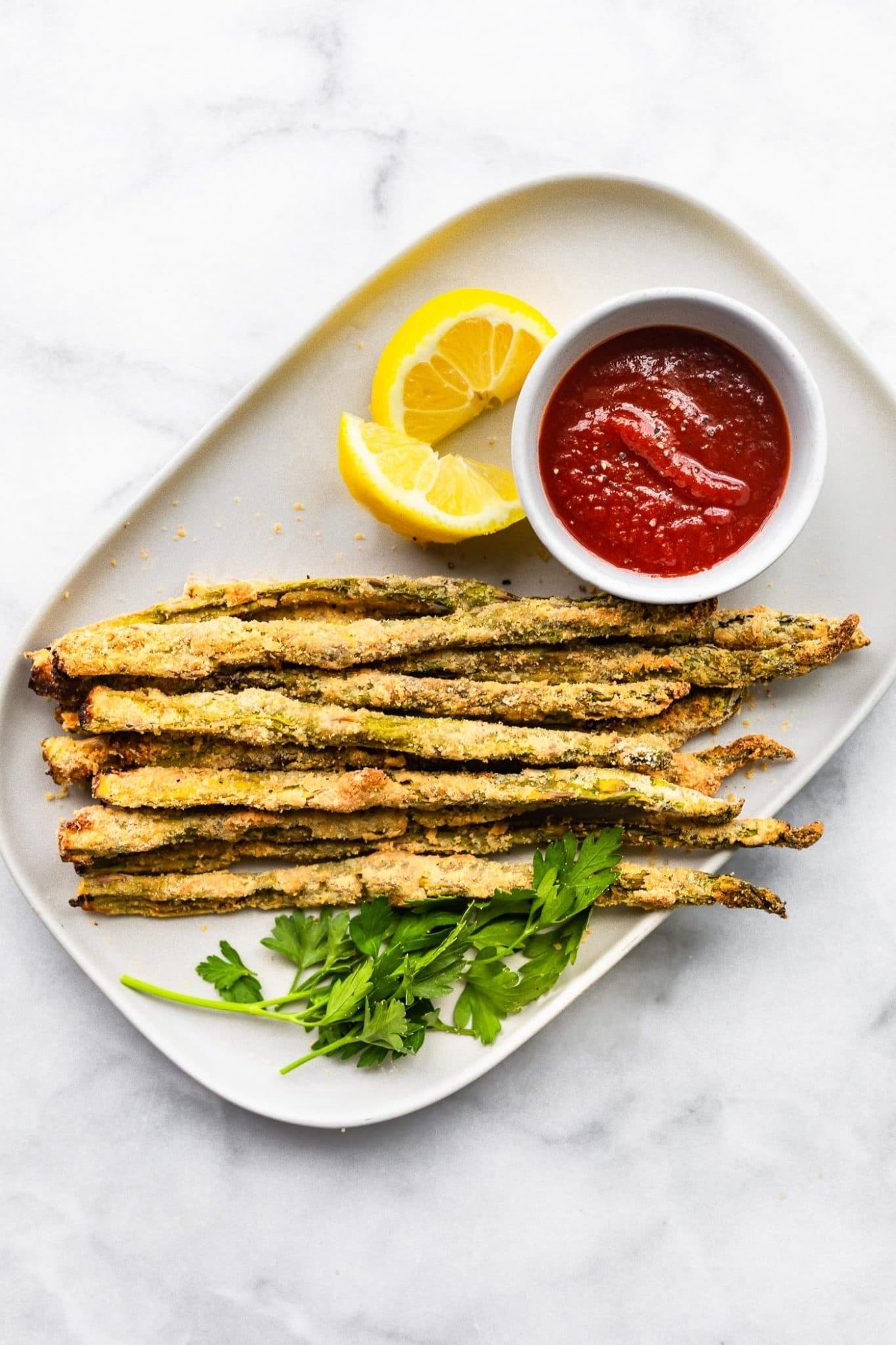 a serving platter of Air Fryer Asparagus Fries with ketchup and lemon wedges on the side