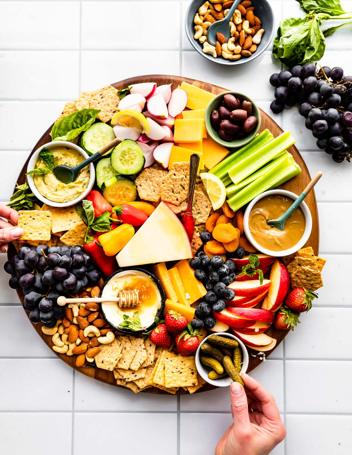 Overhead image of serving platter with crackers, vegetables, fruits, nuts, cheese, and dip.