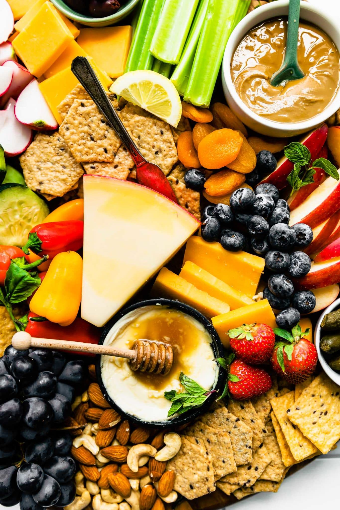 Overhead image of snack board with crackers, cheese, fresh produce, and homemade dips.