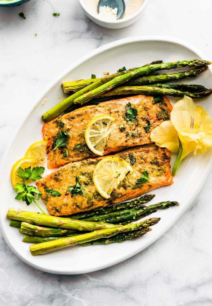 Baked salmon filets surrounded by roasted asparagus and topped with lemon slices and parsley