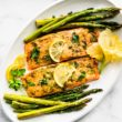 overhead photo of salmon on baking white placec with asparagus on the side
