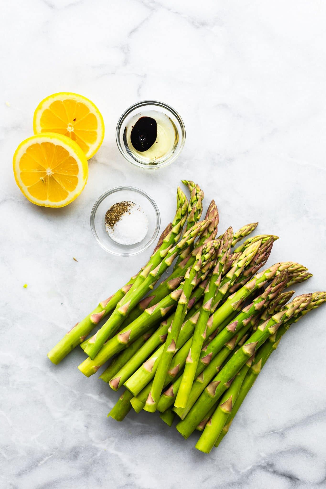 An overhead image of raw asparagus, lemon, salt, pepper, oil and balsamic vinegar.