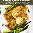 Baked salmon filets surrounded by roasted asparagus and topped with lemon slices and parsley. Title of recipe on top with banner in black