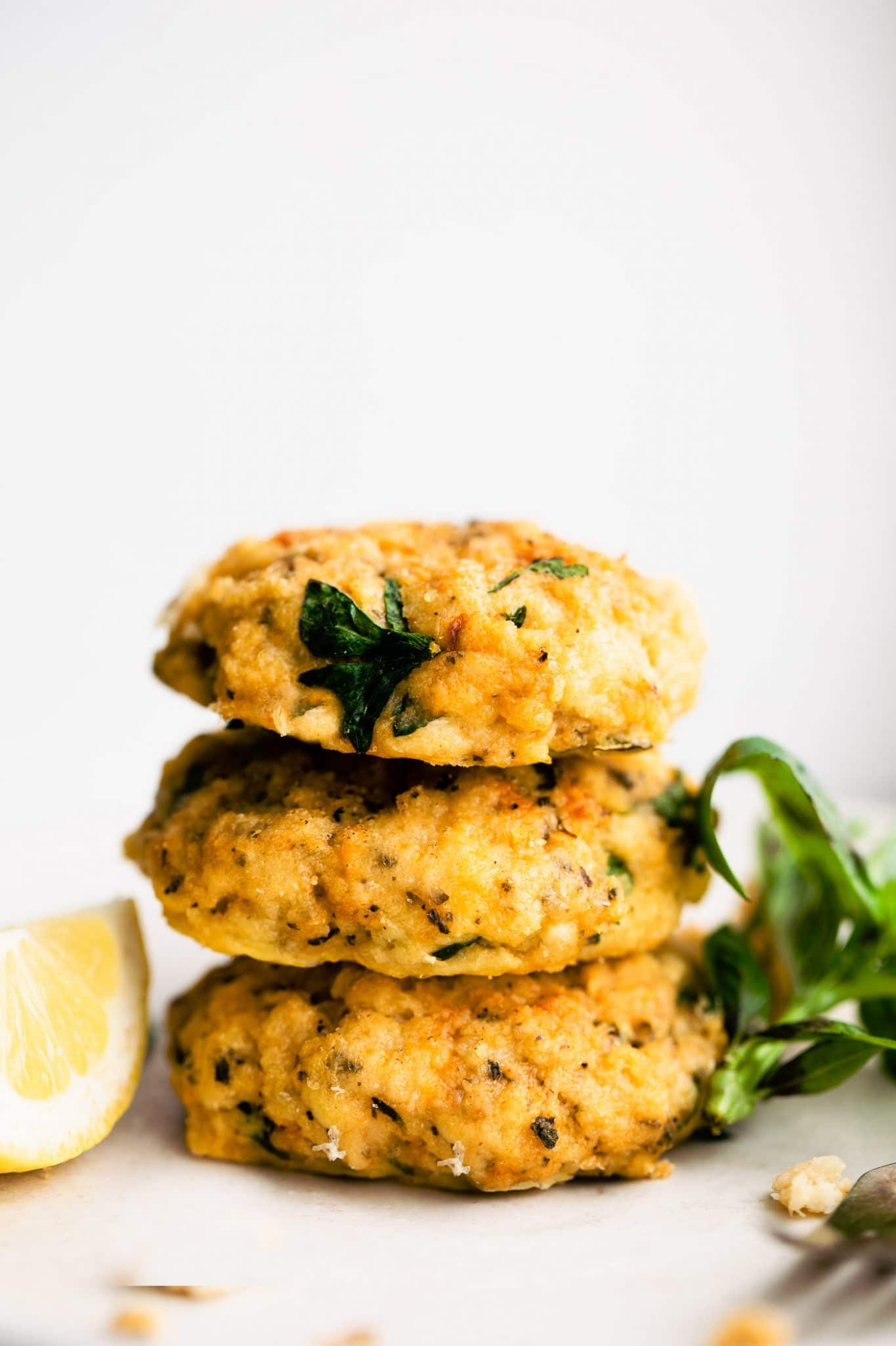 A side image of three cod cakes stacked on top of each other with fresh parsley and lemon on the side.
