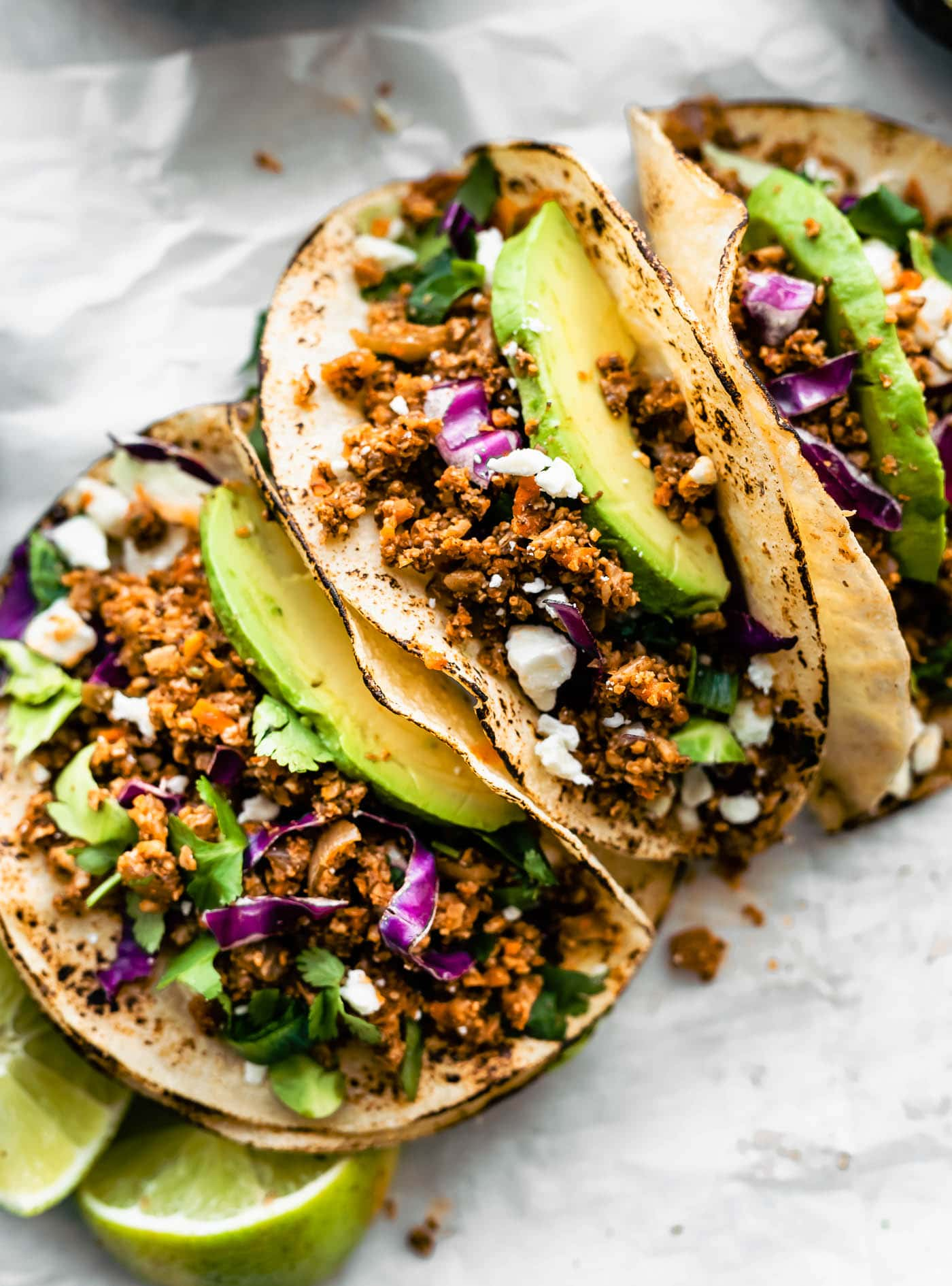 Close up image of charred tortillas with vegan taco meat served as soft shell tacos with purple cabbage and avocado slices.