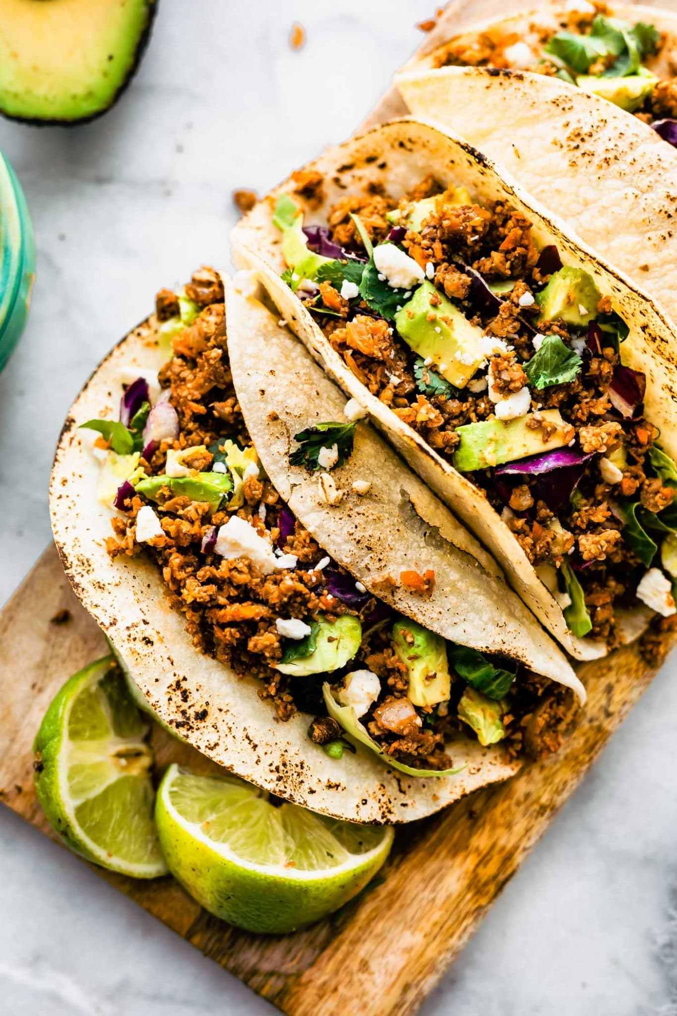 Overhead close up image of vegan taco meat in tortillas with avocado, cilantro, lime wedges, on a wooden platter.