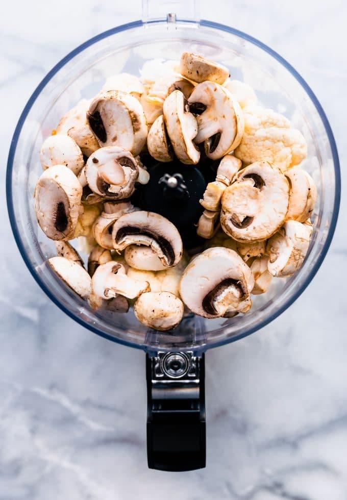 Overhead image of food processor with cauliflower florets and mushroom slices.